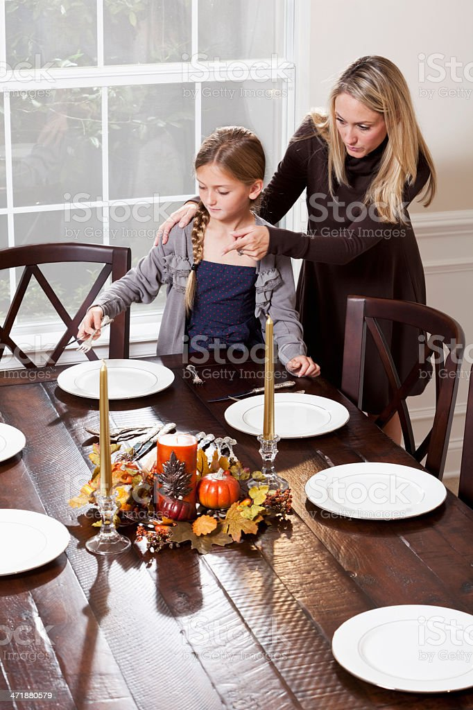 Girl helping mother set the table for dinner stock photo