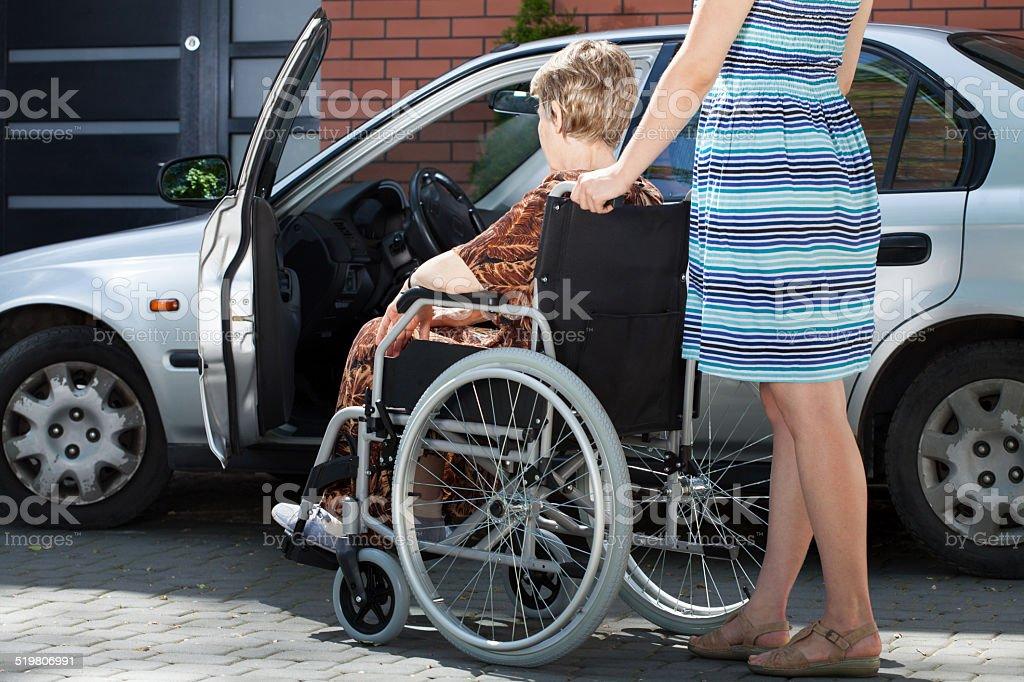 Filles aidant femme sur fauteuil roulant se déplacer dans une voiture - Photo de Adulte libre de droits
