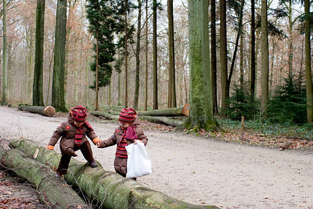 girl helps friend in forest stock photo