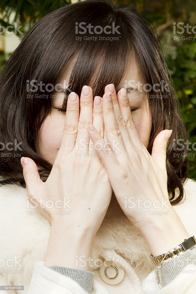 Girl Hides Her Face in Hands stock photo