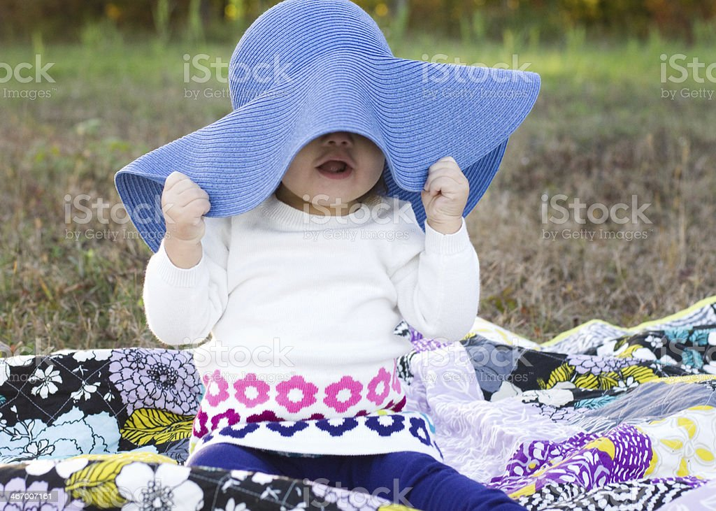 girl hides under large blue hat playing 'peek a boo' royalty-free stock photo