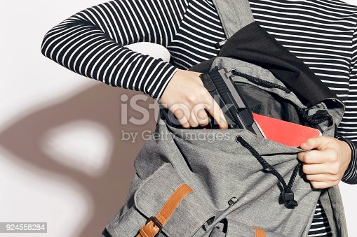 Girl hiding a gun in her school backpack. Concealed carry weapon for protection themselves concept. Indoors, over a white wall.