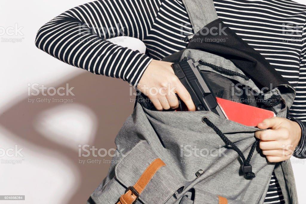 Fille de cacher une arme dans son sac à dos d'école. - Photo