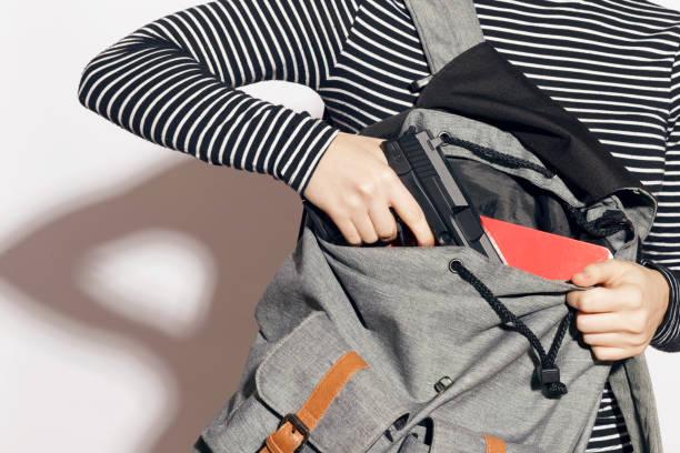 Muchacha de esconder un arma en su mochila escolar. - foto de stock