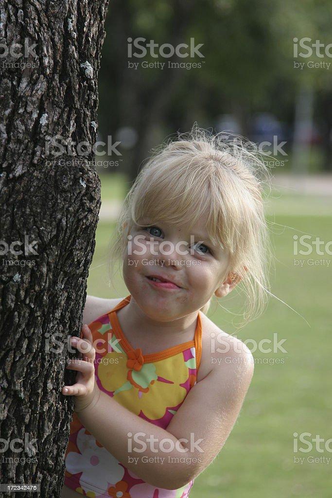 Girl Hiding Behind Tree stock photo