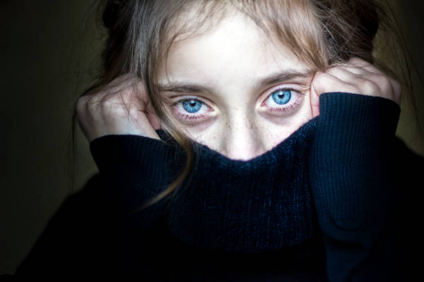 flickan gömmer hennes ansikte. - hand tänder ett ljus bildbanksfoton och bilder