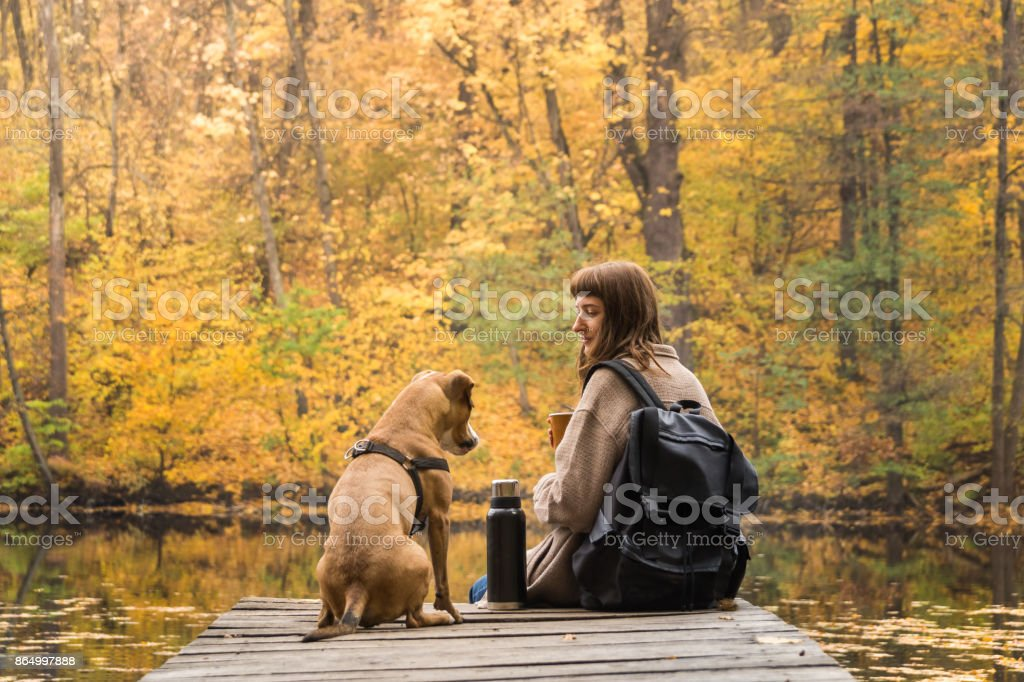 Girl hiker rests at riverbank with her pet dog and drinks coffee from thermos stock photo