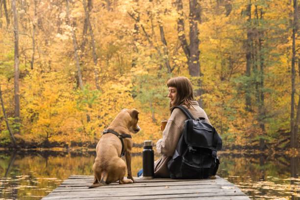 Randonneur fille repose au bord de la rivière avec son chien et boit du café de thermos - Photo