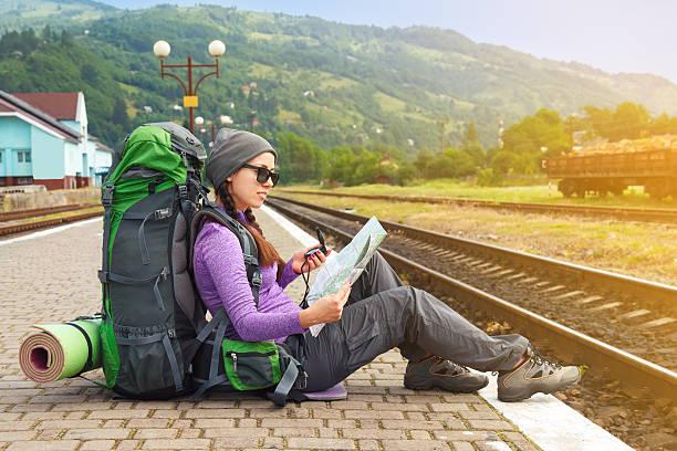 girl hiker waiting train at the railway station - mochilero fotografías e imágenes de stock
