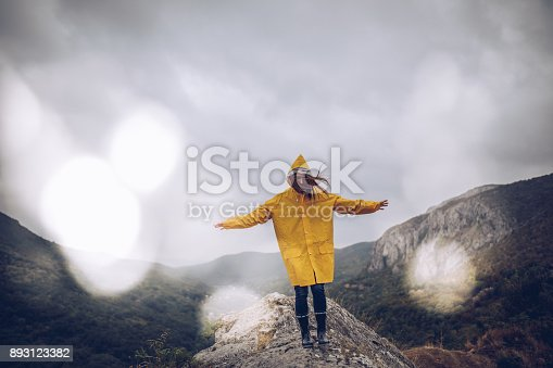 One woman, walking on mountain on a rainy day in yellow raincoat.