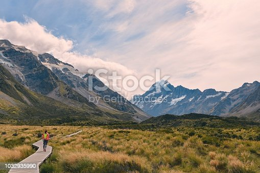 Girl hikes along the boardwalk towards the snow capped mountains of Mount Cook on the Hooker Valley Trail.