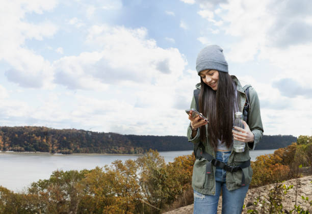 Girl hiking outside in nature using smart phone