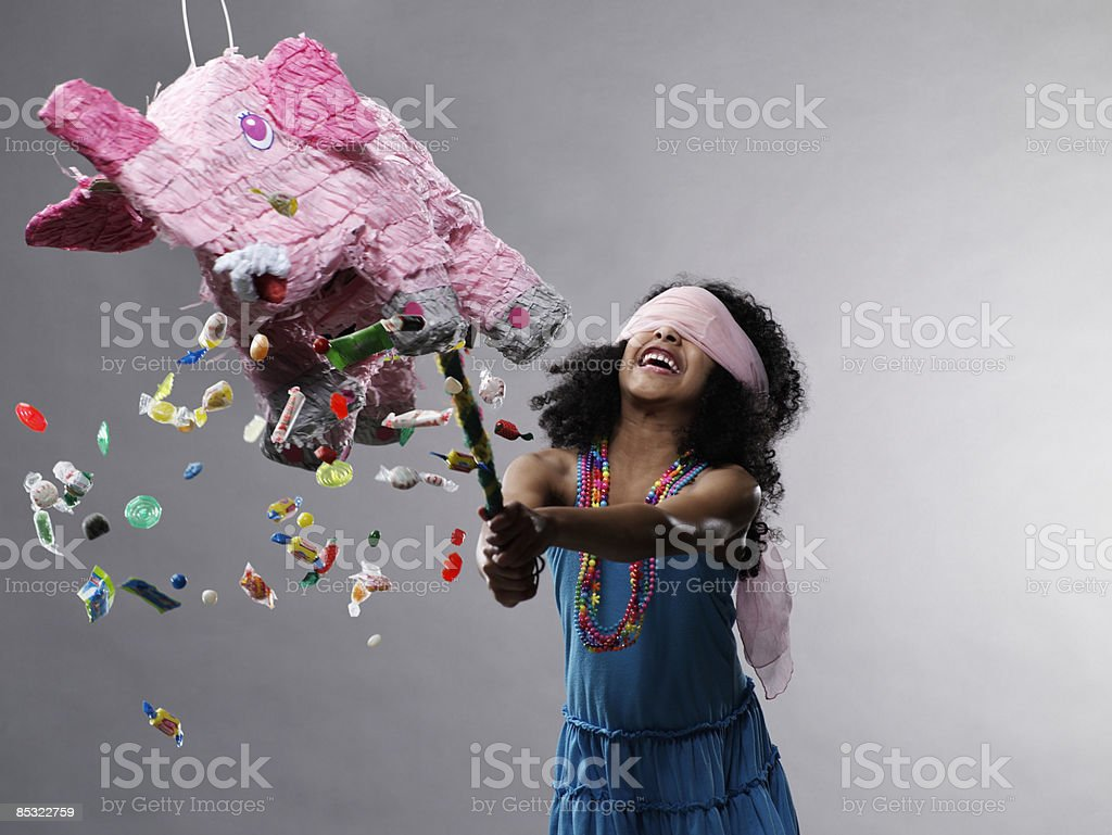 Girl hitting pinata, candy flying royalty-free stock photo