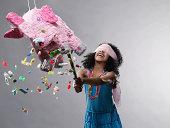Girl hitting pinata, candy flying