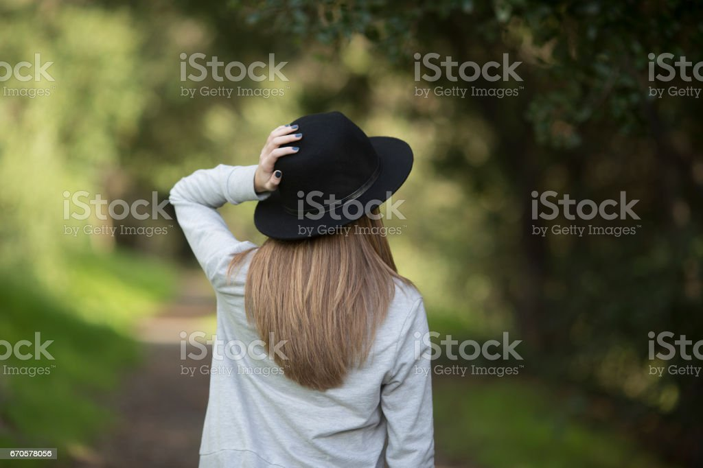 Girl hold her hat on a trail stock photo