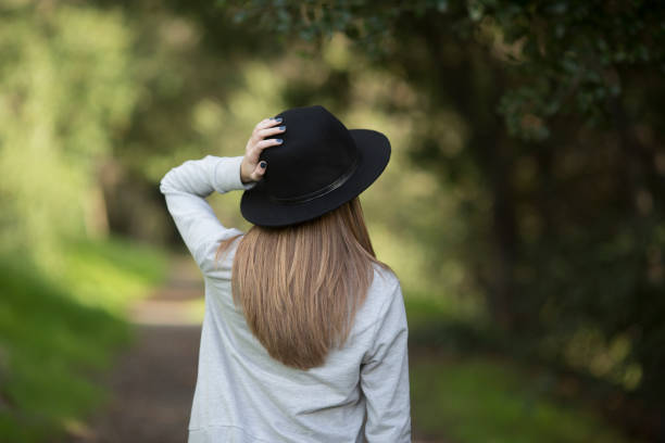 Girl hold her hat on a trail girl walking on wooded trail jude beck stock pictures, royalty-free photos & images
