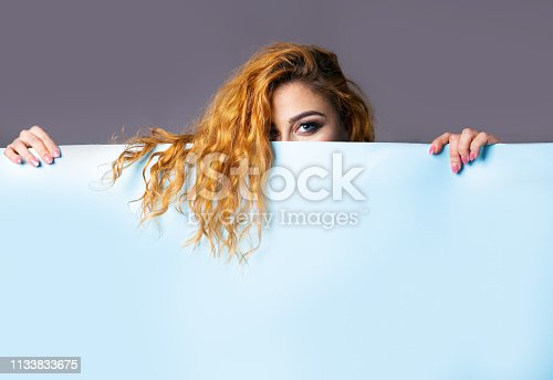 Beautiful girl photographed in a studio with an empty sheet for possible advertising writing.