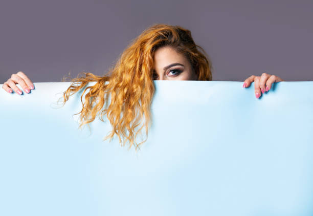 Girl holding a blue paper with empty space. stock photo