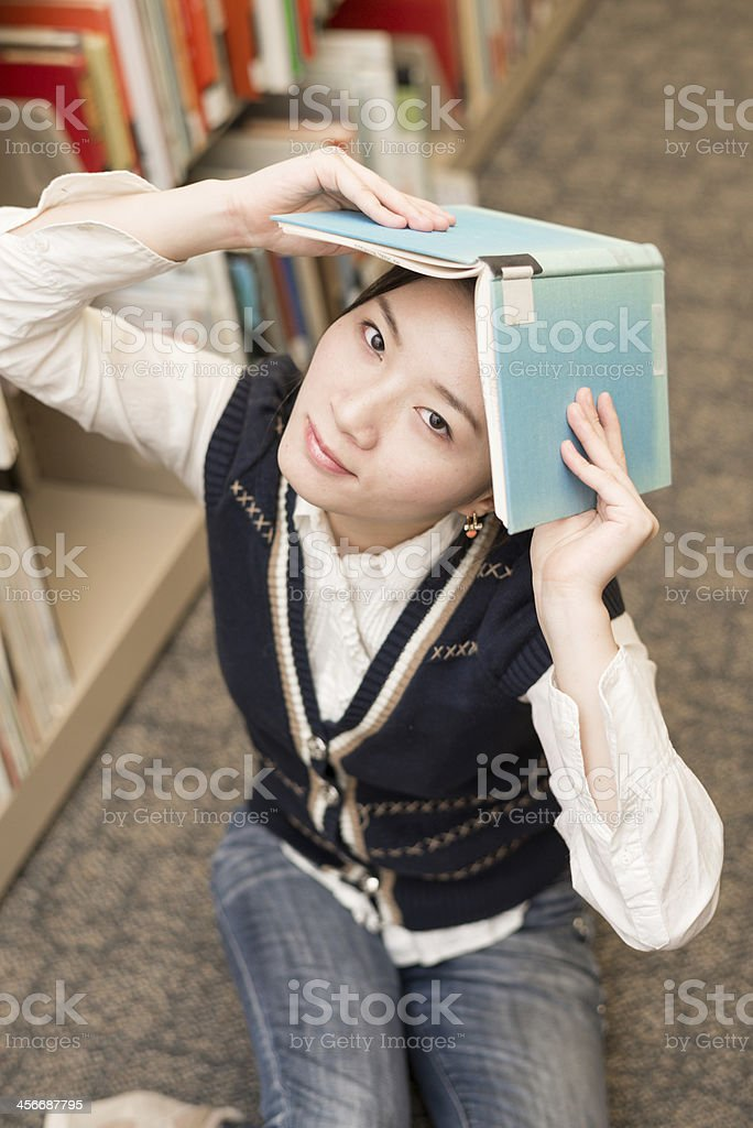 Girl holding a book over head near bookshelf royalty-free stock photo