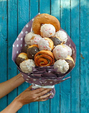 istock Girl holding a Bouquet made from different tasty buns and doughnuts on a blue wooden background 1041186106