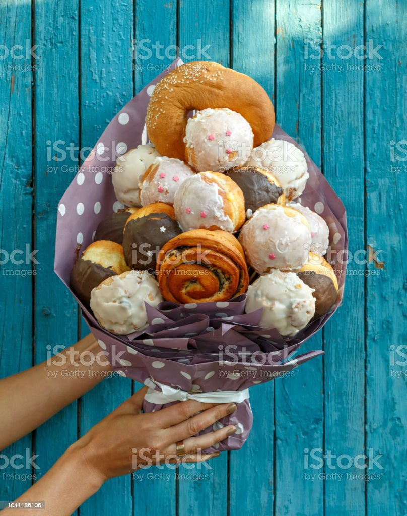 Girl holding a Bouquet made from different tasty buns and doughnuts on a blue wooden background stock photo
