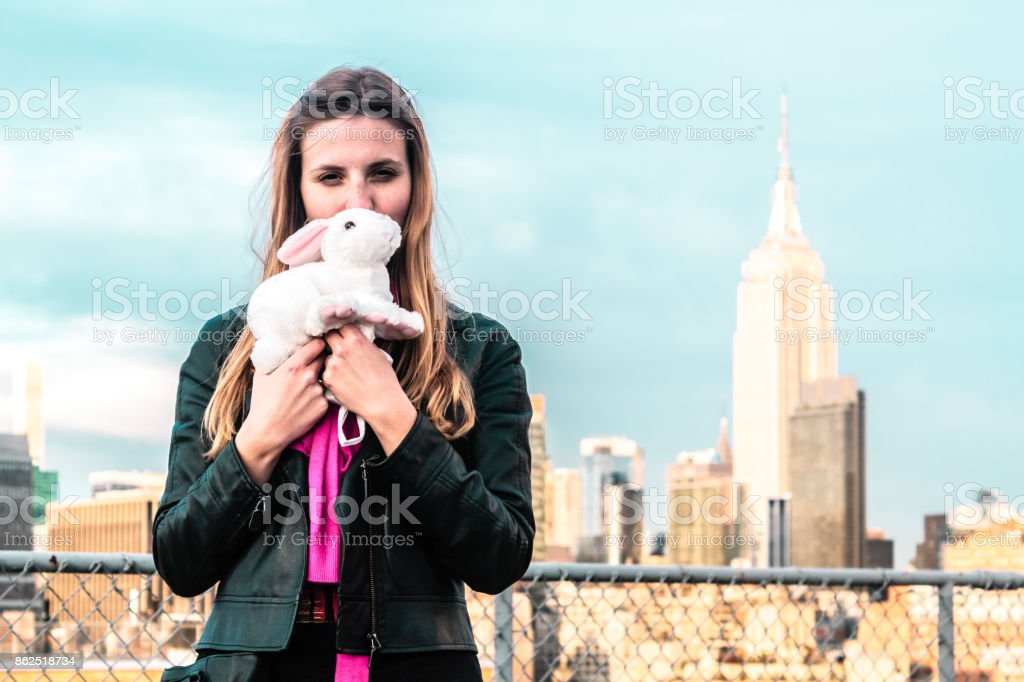 Girl holding a bunny with Empire State at the Background in Manhattan, New York City stock photo
