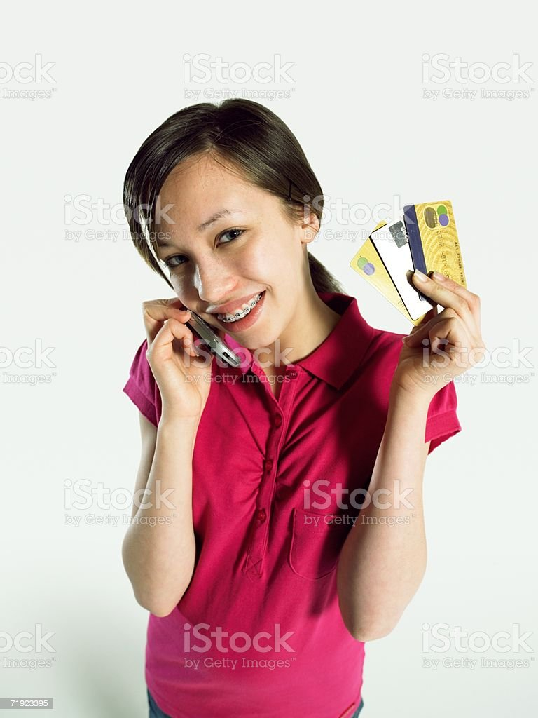 Girl holding a cell phone and credit cards royalty-free stock photo