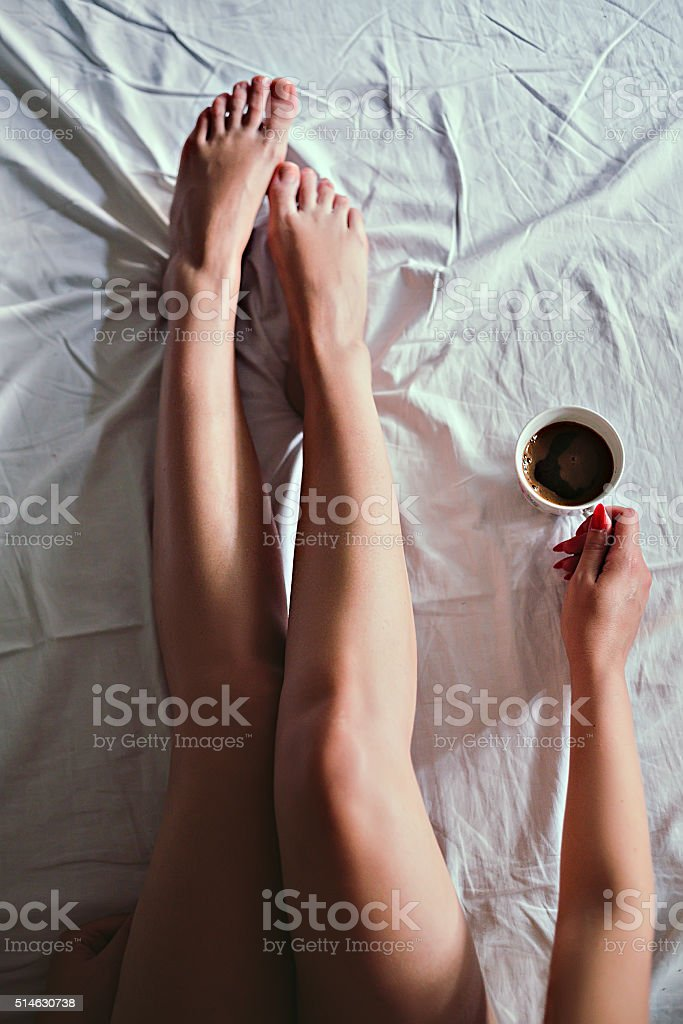 Girl holding a cup of coffee on the bed stock photo