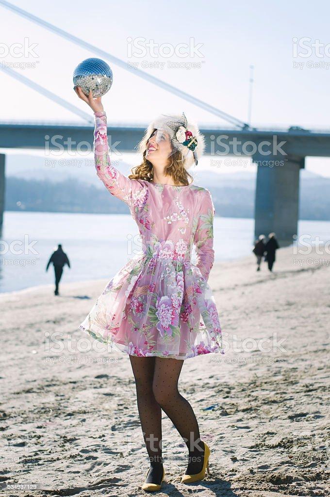 Girl holding a disco ball stock photo