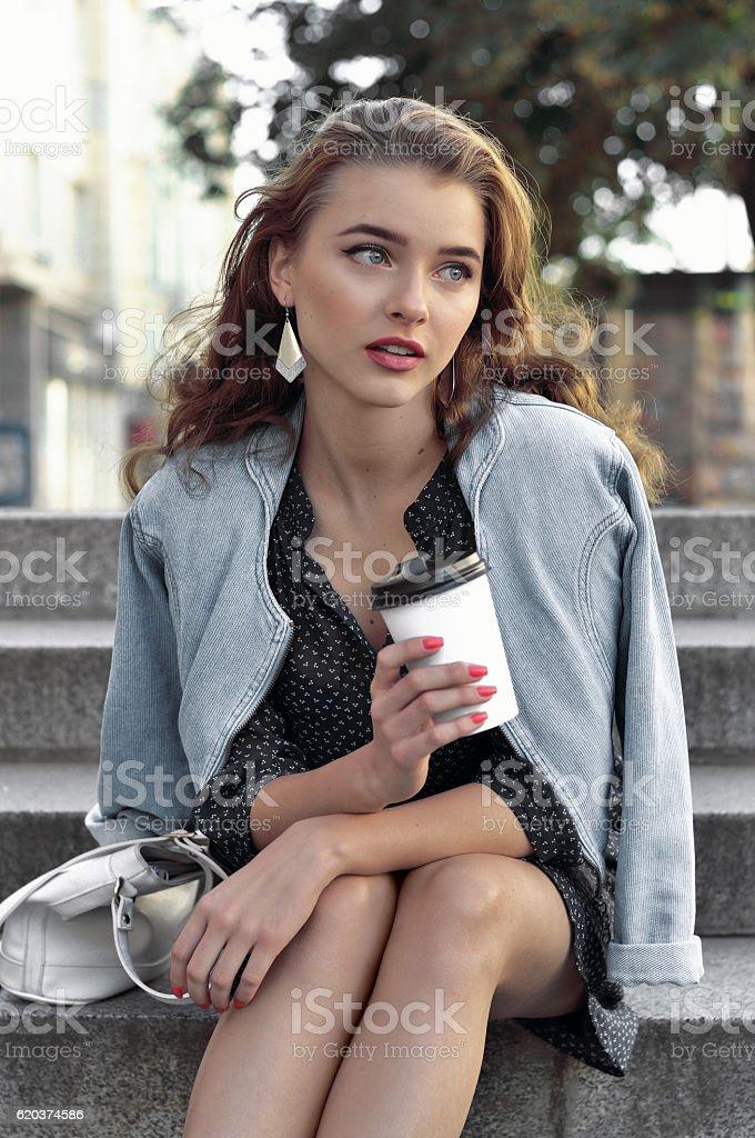 Girl holding a glass with a drink in her hand zbiór zdjęć royalty-free