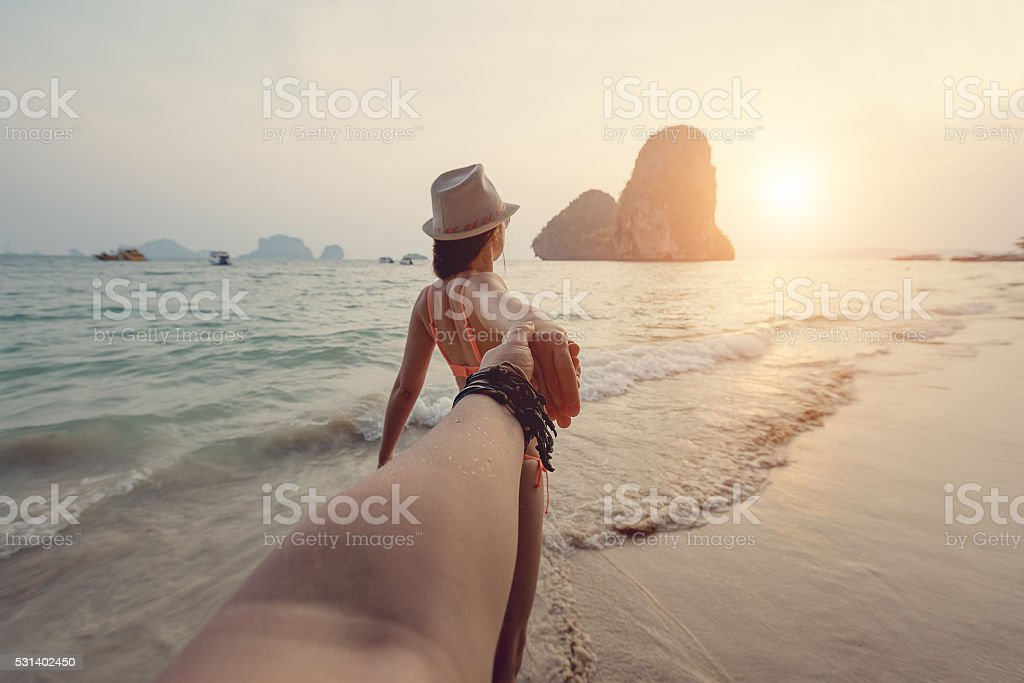 Girl holding a guy's hand on the beach stock photo