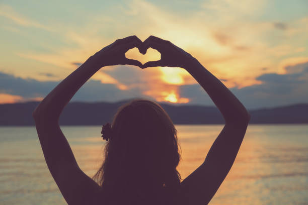 girl holding a heart shape for the ocean / sea. - aura stock photos and pictures