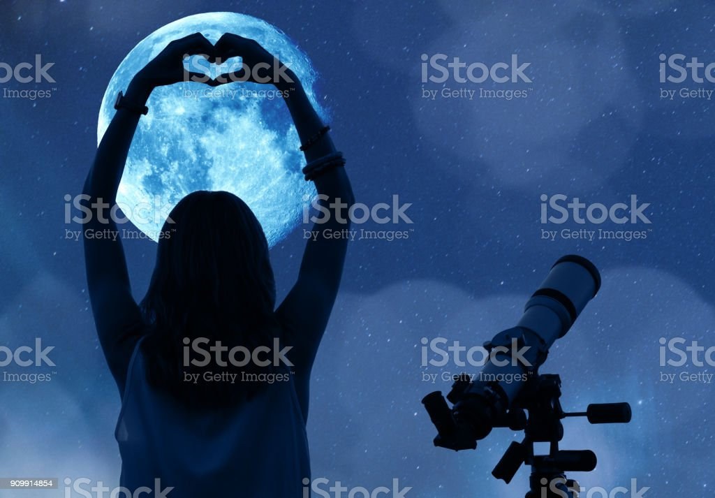 Girl holding a heart - shape with telescope, Moon and stars. My astronomy work. stock photo
