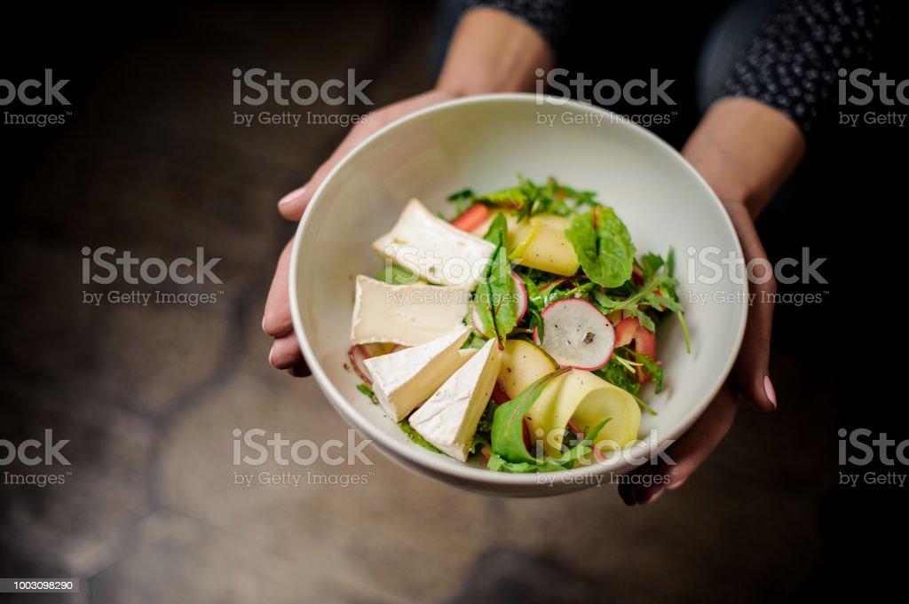 Menina segurando um prato de salada deliciosa - foto de acervo