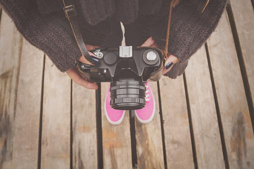 Girl holding a retro camera.