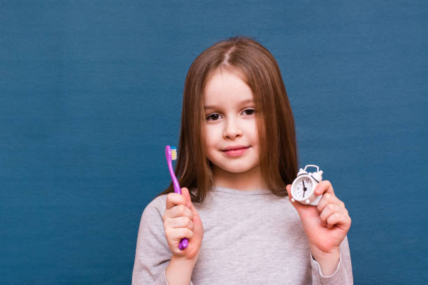 Elinde diş fırçası ve mavi arka planda çalar saat tutan bir kız. Çocuklarda ağız hijyeni kavramı stok fotoğrafı