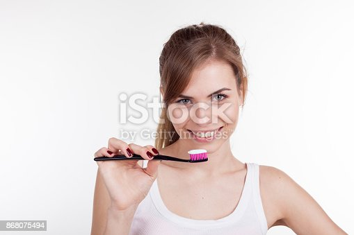 637874676istockphoto girl holding a toothbrush smiles 868075494