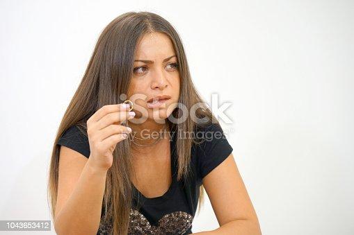 874218810 istock photo A girl holding a wedding ring doubtfully 1043653412