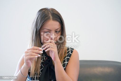 874218810 istock photo A girl holding a wedding ring doubtfully 1069310128