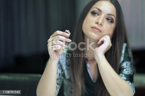 874218810 istock photo A girl holding a wedding ring doubtfully 1128751242