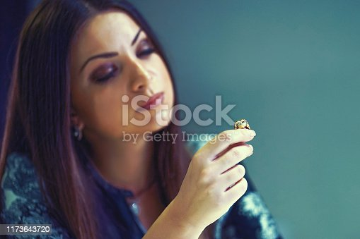 874218810 istock photo A girl holding a wedding ring doubtfully 1173643720
