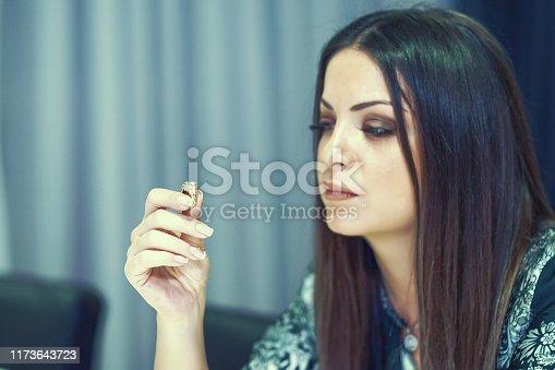 874218810 istock photo A girl holding a wedding ring doubtfully 1173643723