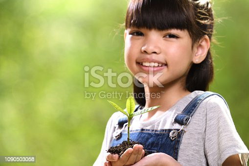 istock A girl holding a young plant in her hands 1090503058