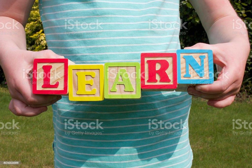 Girl holding alphabet wooden blocks - foto de stock