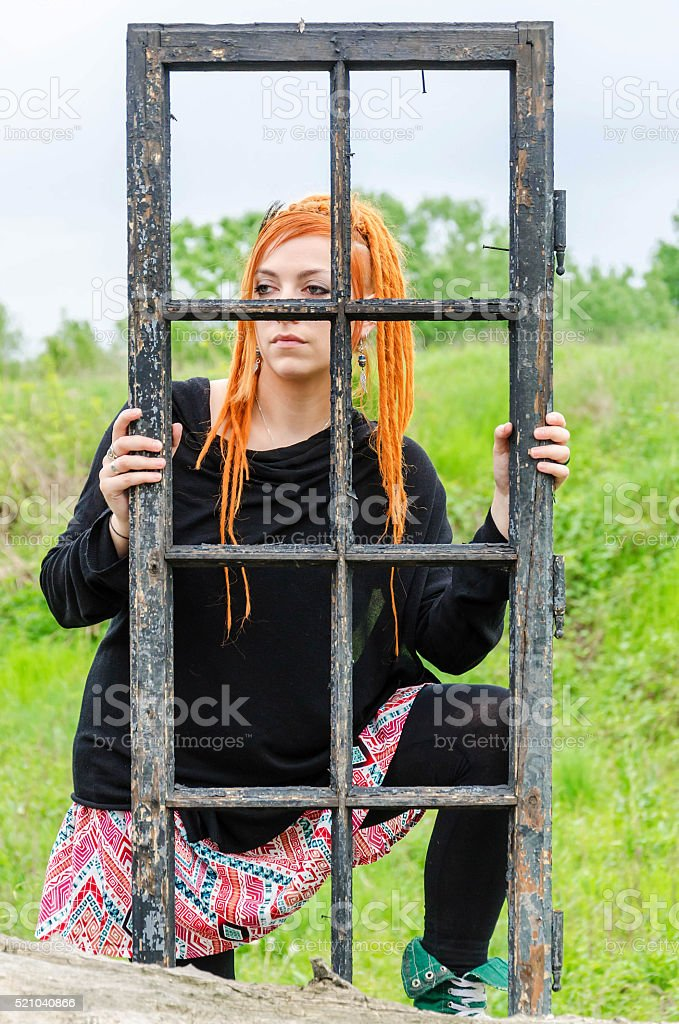 Girl holding an old burnt window stock photo