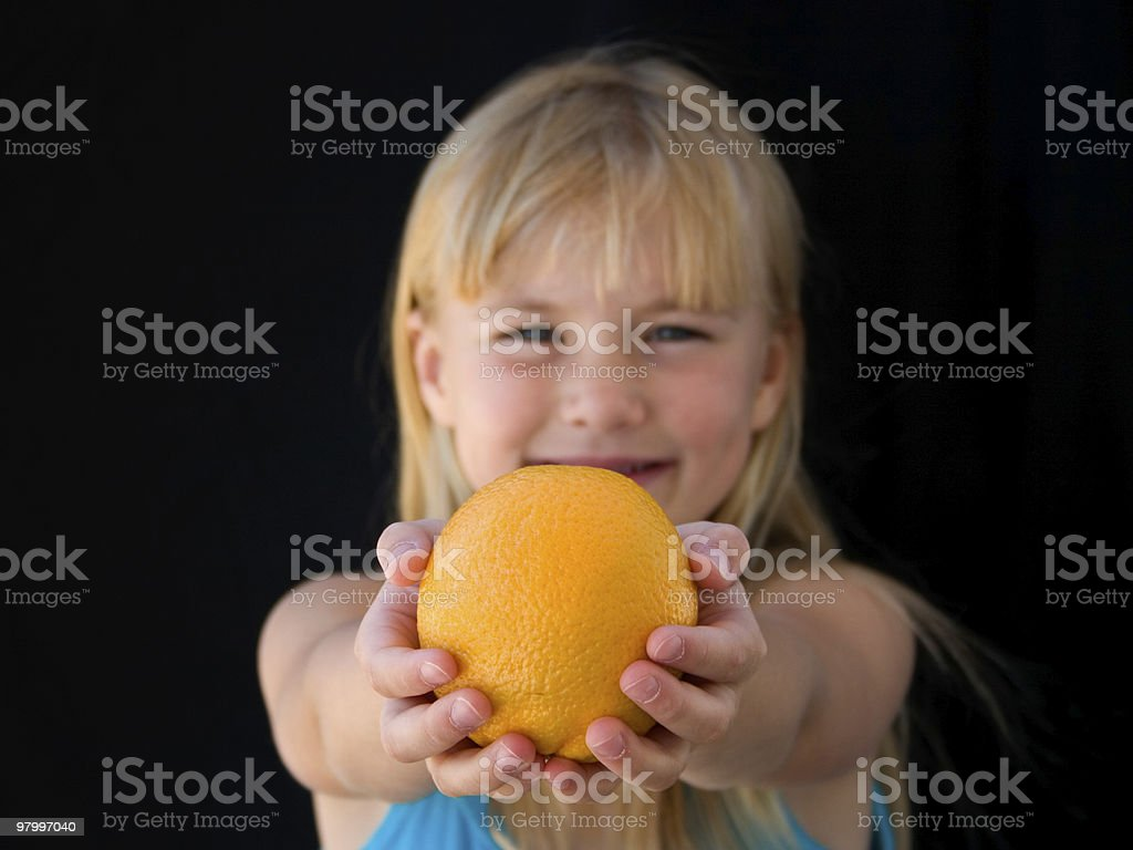 Girl holding an orange royalty free stockfoto