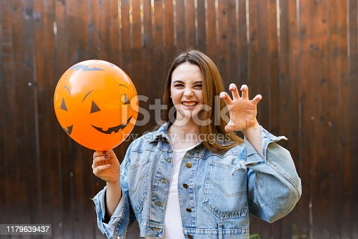girl holding ballon with pumpkin face, copy space. halloween background