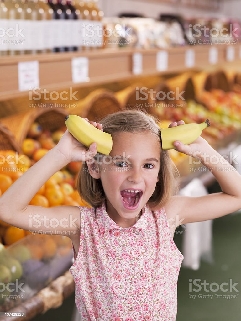Girl holding bananas as horns in grocery store royalty-free stock photo