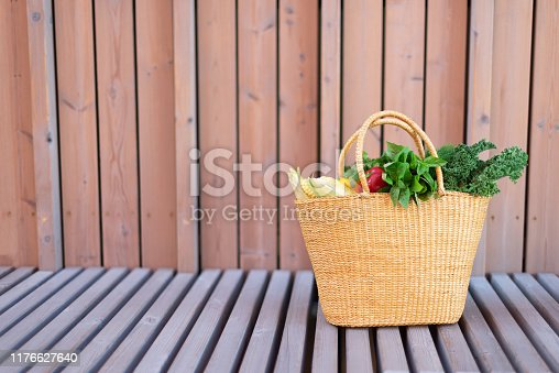 istock Girl holding basket with healthy organic vegetables, wooden background, copy space. Autumn harvest. Zero waste, plastic free concept. Sustainable lifestyle. Thanksgiving day 1176627640