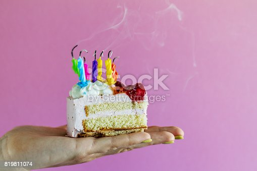 istock Girl holding beautiful appetizing birthday cake with many blown candles. Closeup. 819811074
